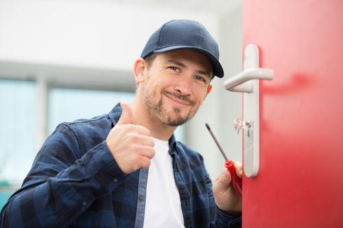 Professional locksmith holding screwdriver and giving thumbs up